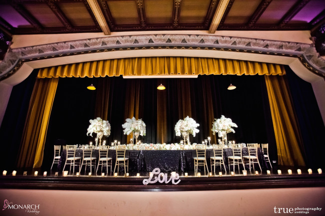 Gatsby-Prado-at-balboa-park-wedding-large-headtable-on-stage-uplights